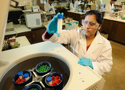 woman working with a centrifuge in the National Center for Natural Products Research