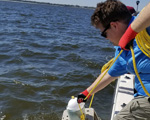Graduate assistant pulling sensory landers into a boat